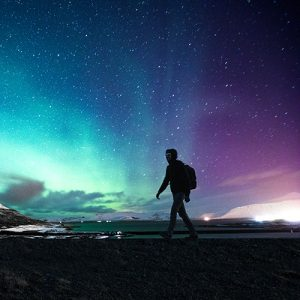 Solo traveller walking in front of the northern lights.