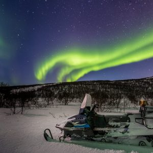 Green northern lights and snowmobile on foreground