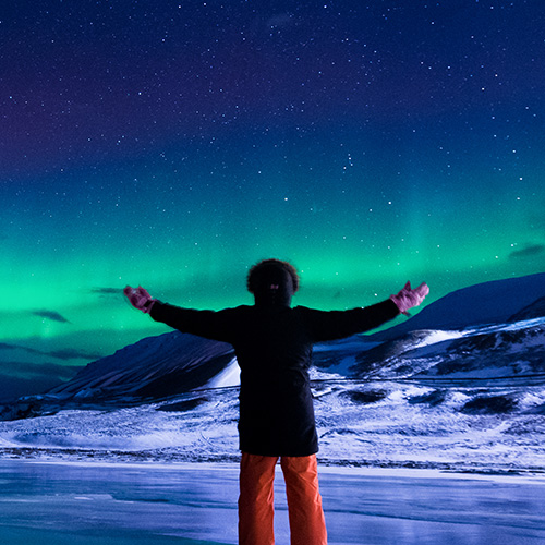 Man gazing at the Arctic northern lights